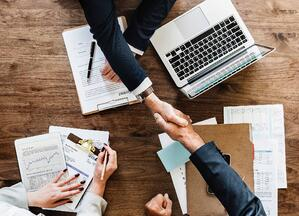 A sales meeting ending on an agreement and a handshake seen from above