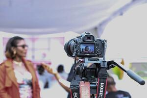 Digital camera filming a woman being interviewed